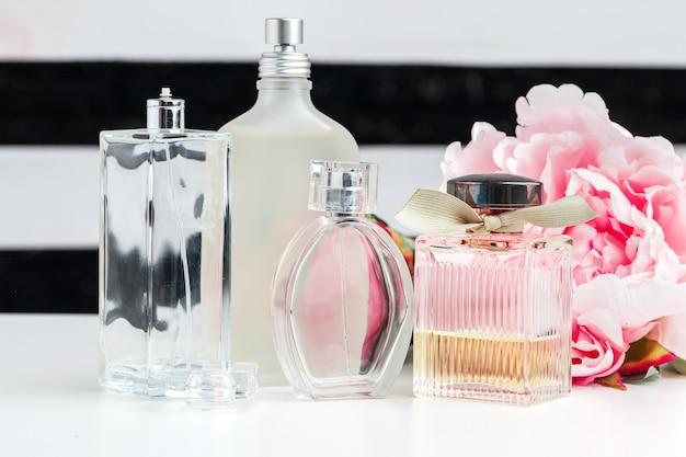 Bouteilles de parfum avec des fleurs sur blanc
