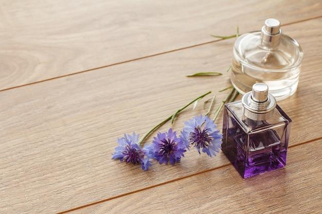 Bouteilles de parfums avec des fleurs de centaurée sur des planches en bois