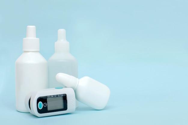 Bouteilles en plastique blanc de médicaments et oxymètre de pouls sur fond bleu