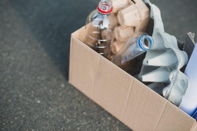 Bouteilles en plastique et cartons d'oeufs sur une boîte en carton recyclée