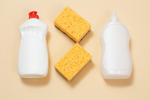 Bouteilles en plastique de liquide vaisselle, détergent pour fours à micro-ondes et cuisinières et éponges sur une surface beige