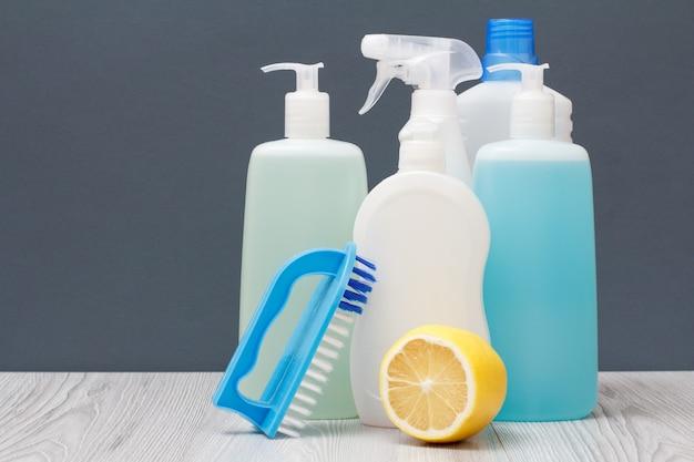 Bouteilles en plastique de liquide vaisselle, nettoyant pour vitres et carreaux, détergent pour fours à micro-ondes et cuisinières, brosse et citron sur fond gris. concept de lavage et de nettoyage.