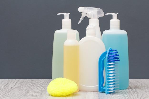 Bouteilles en plastique de liquide vaisselle, nettoyant pour vitres et carreaux, détergent pour fours à micro-ondes et cuisinières, brosse et éponge sur fond gris. concept de lavage et de nettoyage.