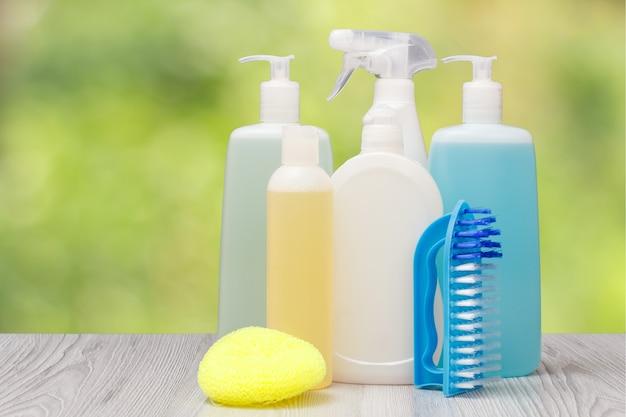 Bouteilles en plastique de liquide vaisselle, nettoyant pour vitres et carreaux, détergent pour fours à micro-ondes et cuisinières, brosse et éponge sur fond naturel flou. concept de lavage et de nettoyage.
