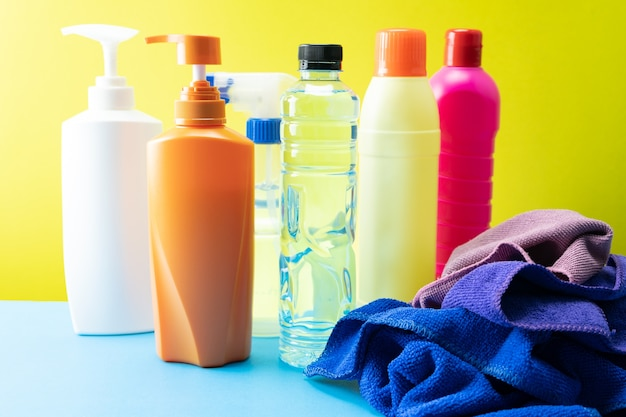 Bouteilles en plastique de produits de nettoyage sertie de vêtements de pile sur fond de table.