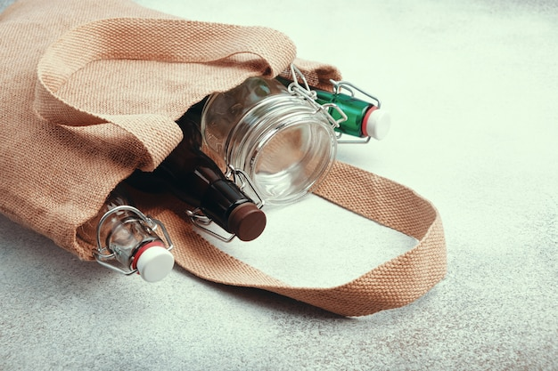 Bouteilles et pots en verre réutilisables dans un sac de jute.