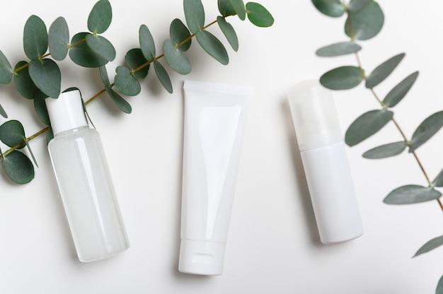 Bouteilles de produits cosmétiques sur la vue de dessus de fond blanc. crème pour le visage, masque.