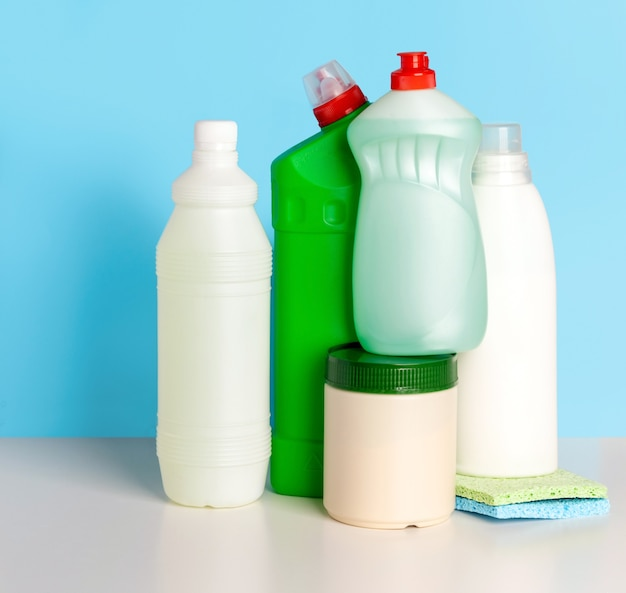 Bouteilles de produits de nettoyage pour la maison sur bleu