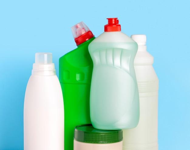 Bouteilles de produits de nettoyage pour la maison sur fond bleu. nettoyage de l'appartement. détergent pour vaisselle, toilette, poudre, javellisant