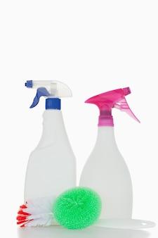Bouteilles de pulvérisation rose et bleu et une brosse