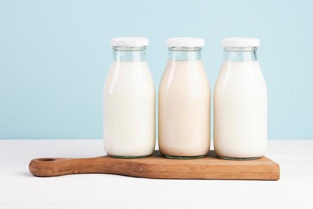 Bouteilles remplies de lait sur une planche à découper