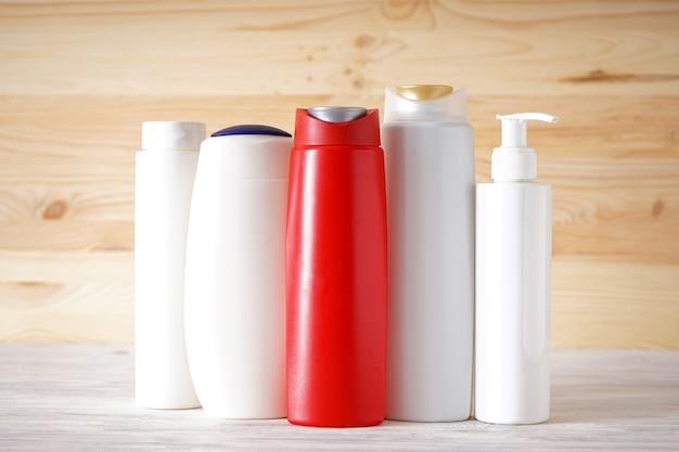 Bouteilles de savon et de shampoing. différentes bouteilles cosmétiques sur fond en bois.