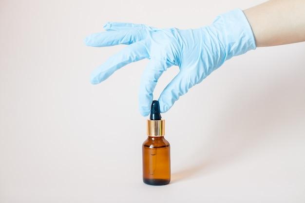 Bouteilles de sérum pour le visage dans ses mains dans des gants de protection en caoutchouc médical sur gris