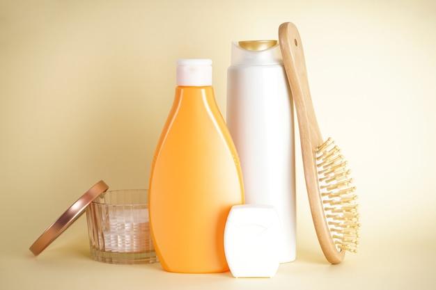 Bouteilles de shampoing, distributeur de savon et brosse à cheveux en bois sur fond jaune.