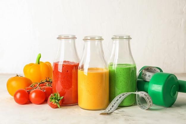 Bouteilles avec smoothies frais et savoureux, ingrédients, haltères et ruban à mesurer sur table. notion de régime