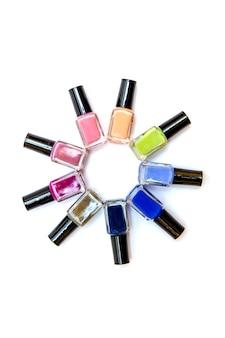 Bouteilles de vernis à ongles colorées empilées cercle sur fond blanc