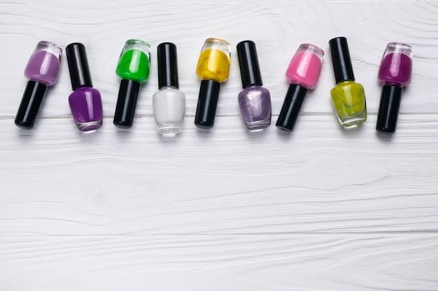 Bouteilles de vernis à ongles de différentes couleurs sur un fond en bois blanc