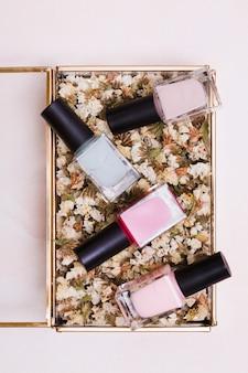 Bouteilles de vernis à ongles roses et gris sur une boîte de limonium blanc séché sur un fond coloré