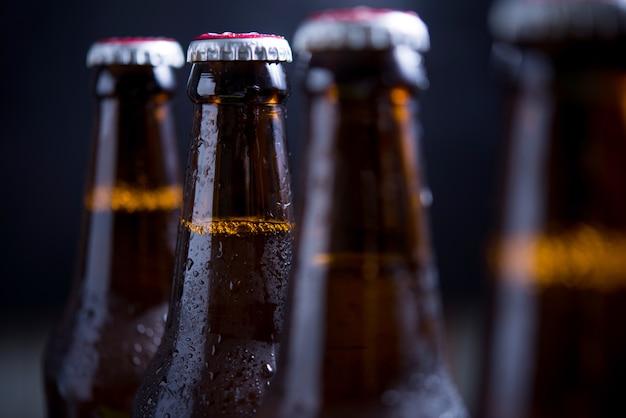 Bouteilles en verre de bière avec verre et glace sur fond sombre