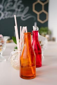 Bouteilles en verre colorées lumineuses avec des pailles en papier pour des boissons ou des cocktails lors d'une fête