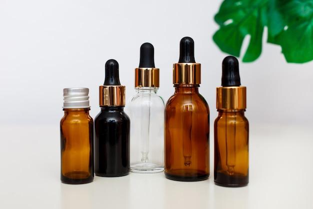 Les bouteilles en verre compte-gouttes se moquent. pipette cosmétique sur fond blanc avec congé tropical.