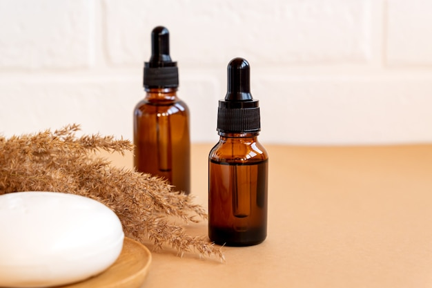Bouteilles en verre foncé avec huiles essentielles et barre de savon pour le visage sur fond beige. concet de soins de la peau avec copie soace. cosmétiques naturels