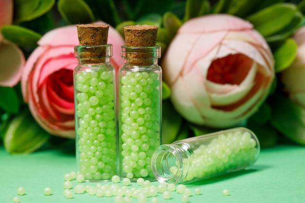 Bouteilles en verre avec des granules verts avec des roses. remèdes homéopathiques