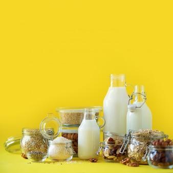 Bouteilles en verre de lait végétal et d'amandes végétaliennes, noix, noix de coco, lait de graines de chanvre sur fond jaune.