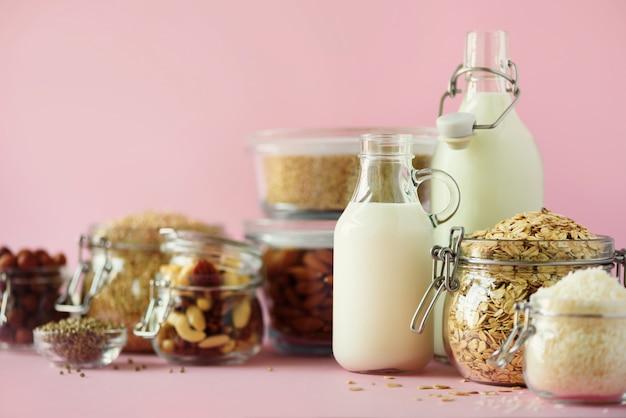 Bouteilles en verre de lait végétal et d'amandes végétaliennes, noix, noix de coco, lait de graines de chanvre sur fond rose.
