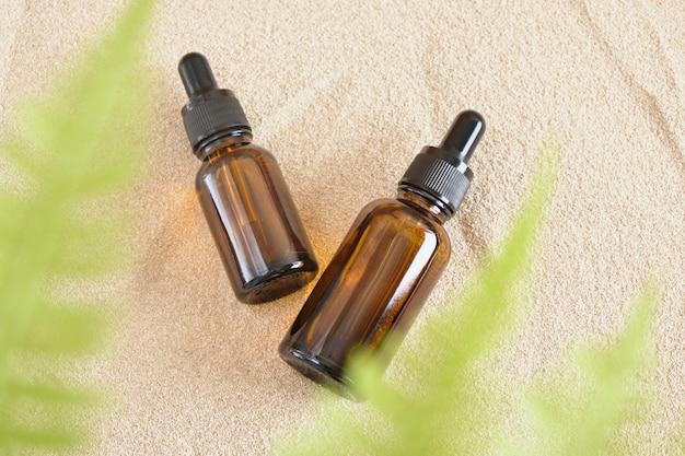 Bouteilles en verre marron avec distributeur compte-gouttes sur fond de sable, bouteilles pour huile cosmétique ou sérum sans logo ni étiquette, produit cosmétique vierge et maquette