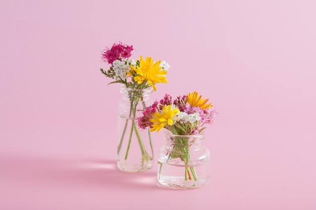 Bouteilles en verre miniatures avec des fleurs sauvages sur une surface rose