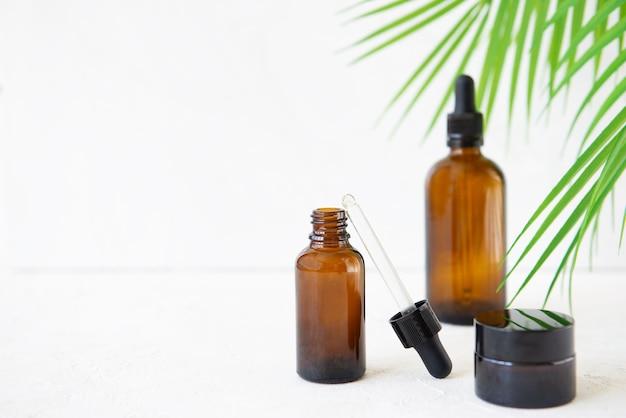 Bouteilles en verre pour huiles de soin ou sérums avec une branche de palmier sur fond blanc