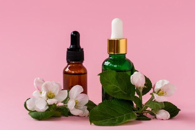 Bouteilles en verre de sérum avec pipette et belle fleur sur fond rose. concept cosmétique de spa bio naturel. vue de face.