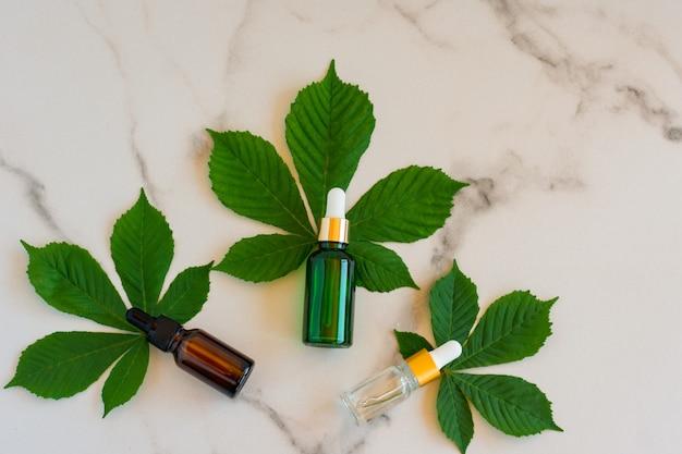 Bouteilles en verre de sérum avec pipette et belles feuilles vertes sur fond blanc. concept cosmétique de spa bio naturel. vue de dessus.