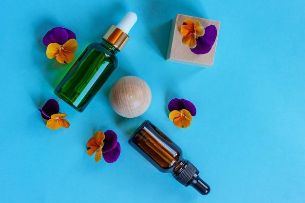 Bouteilles en verre de sérum avec pipette et belles fleurs d'alto sur fond bleu. concept cosmétique de spa bio naturel. vue de dessus.