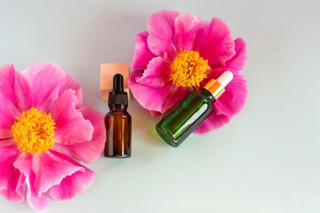 Bouteilles en verre de sérum avec pipette et belles fleurs de pivoine sur fond blanc. concept cosmétique de spa bio naturel. vue de dessus.
