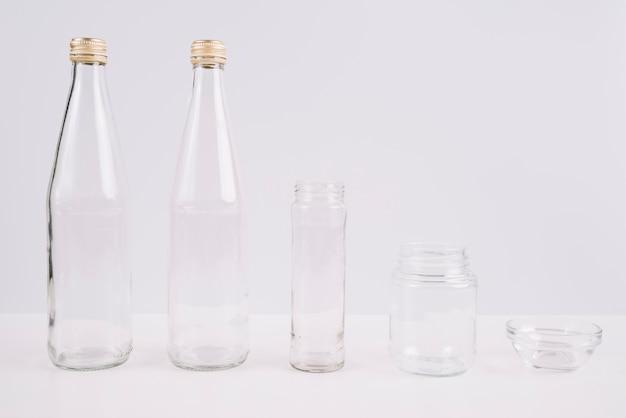 Bouteilles en verre et tasses sur fond blanc