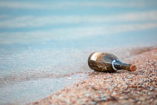 Des bouteilles de verre vert ont été laissées sur la plage.