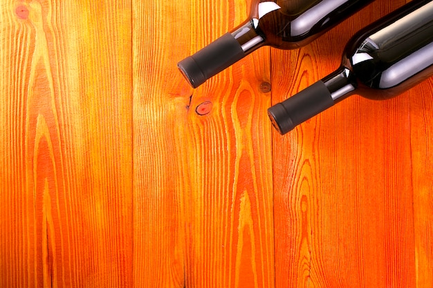 Bouteilles en verre de vin sur fond de table en bois rouge.