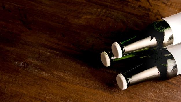 Bouteilles vertes de bière sur une table en bois