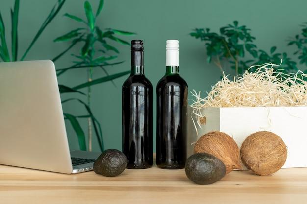 Bouteilles de vin, boîte blanche, ordinateur, noix de coco et avocat sur la table, concept de commande en ligne.