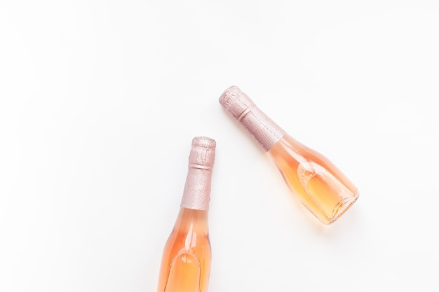 Bouteilles de vin de champagne rose sur fond blanc