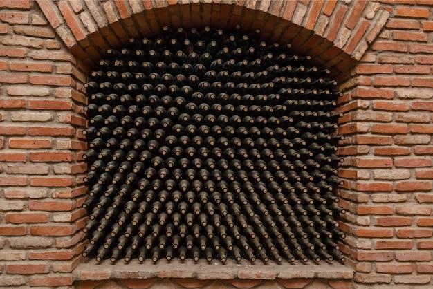 Bouteilles de vin empilées dans la cave, vieilles caves à vin avec bouteilles et barils