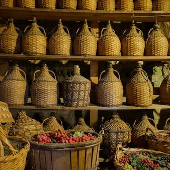 Bouteilles de vin sur des étagères et paniers avec raisins en cave