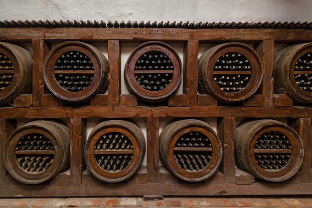Des bouteilles de vin reposent sur des étagères à partir de bûches épaisses, de vieilles caves à vin avec des bouteilles et des tonneaux