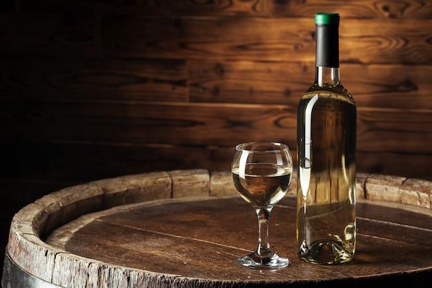 Bouteilles de vin avec verre, fond en bois