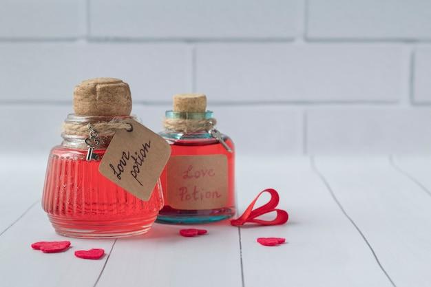 Bouteilles vintage avec des potions d'amour magique sur une table en bois blanc, espace pour le texte