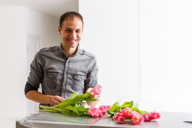 Boutique de livraison de fleurs. fleuriste créant l'ordre, faisant un bouquet de printemps. un mâle fait un bouquet à l'aide de tulipes