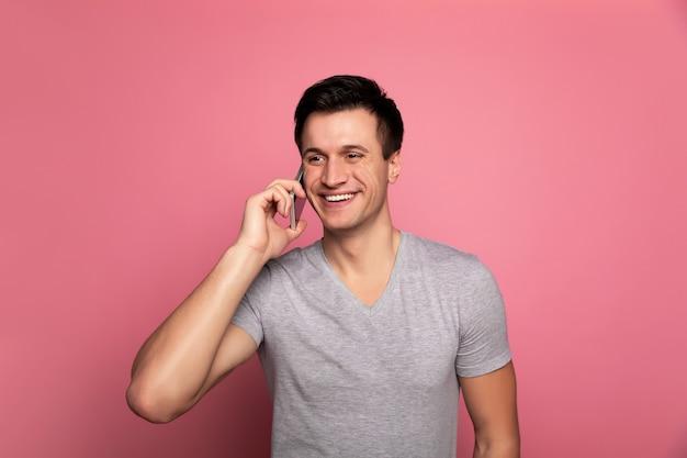 Boutiques parlantes. jeune homme fou de joie dans un t-shirt, qui parle au téléphone, tout en regardant de côté.