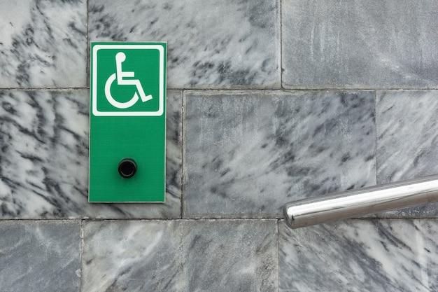 Bouton d'appel du personnel pour les personnes handicapées des panneaux de pochoir à l'entrée d'un bâtiment public